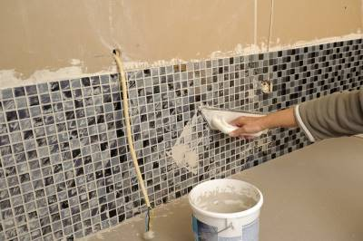 image of a hand applying grout to tile