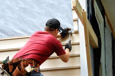 Image of man in red shirt hammering siding